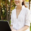 Young pretty woman with laptop sitting on the bench in a park — Stock Photo #6062751