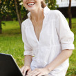 Stock Photo: Young pretty woman with laptop sitting on the bench in a park