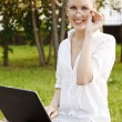 Pretty woman with laptop sitting on the bench. — Stock Photo #6064287