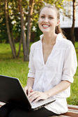 Laughing pretty woman with laptop sitting on the bench — Stock Photo