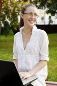 Pretty woman with laptop sitting on the bench. — Stock Photo