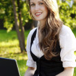 Young pretty woman with laptop sitting on the bench in a park — Stock Photo #6079448