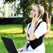 Foto Stock: Young pretty womwith laptop sitting on bench in park.