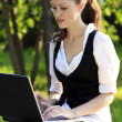 Young pretty woman with laptop sitting on the bench in a park — Stock Photo #6088211