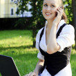 Young pretty woman with laptop sitting on the bench in a park. — Stock Photo #6103438