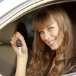Cheerful young lady sitting in a car and showing the key — Foto de Stock