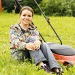 Stock Photo: Young beautiful woman gardening and trimming the lawn
