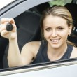 Stock Photo: Beautiful young happy woman in car showing the keys