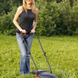 Woman mowing with lawn mower — ストック写真