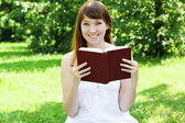 Young female student reading a book outdoors — Stock Photo
