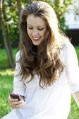 Młoda kobieta czyta sms na telefon komórkowy — Zdjęcie stockowe