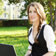 Young pretty woman with laptop sitting on the bench in a park. — Stock Photo
