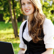 Young pretty woman with laptop sitting on the bench in a park — Stock Photo #6331068