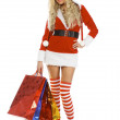 Beautiful blond woman in christmas costume with shopping bags — Stockfoto