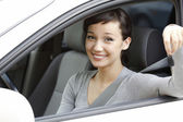 Pretty girl in a car showing the key. — Stock Photo