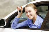 Pretty girl in a car showing the key — Stock fotografie