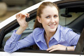 Pretty girl in a car showing the key — Stock Photo