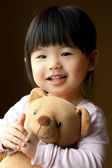 Smiling little child with a teddy bear — Stock Photo