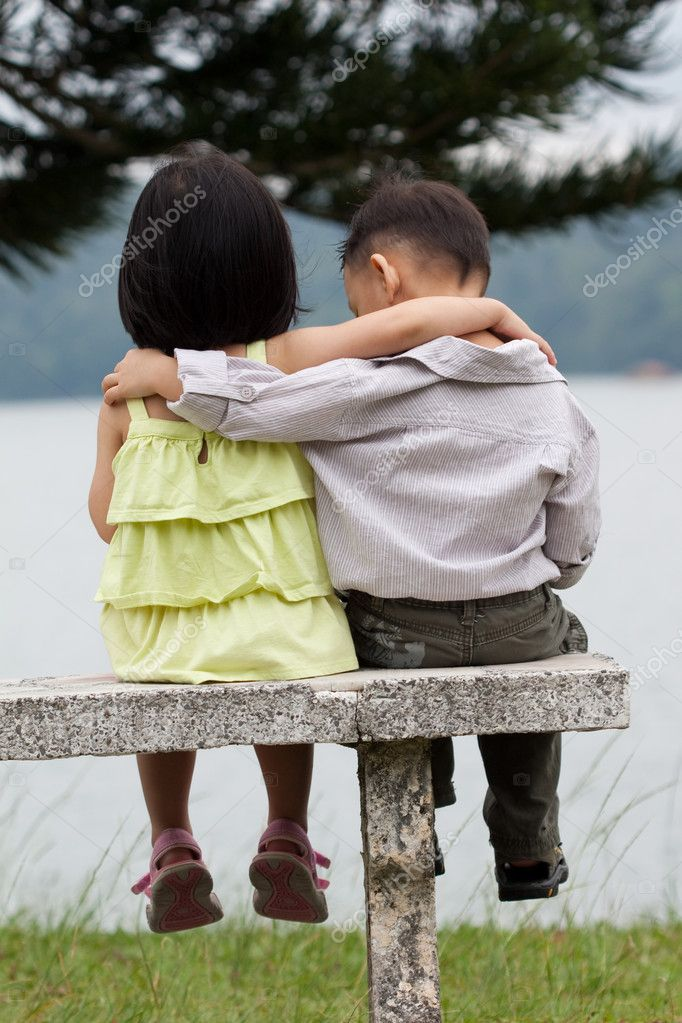 Two little kids dating with hand lifts onto shoulder in a park  Stock Photo #6038574