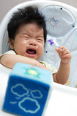 Little Asian baby girl crying on a high chair — Stock Photo