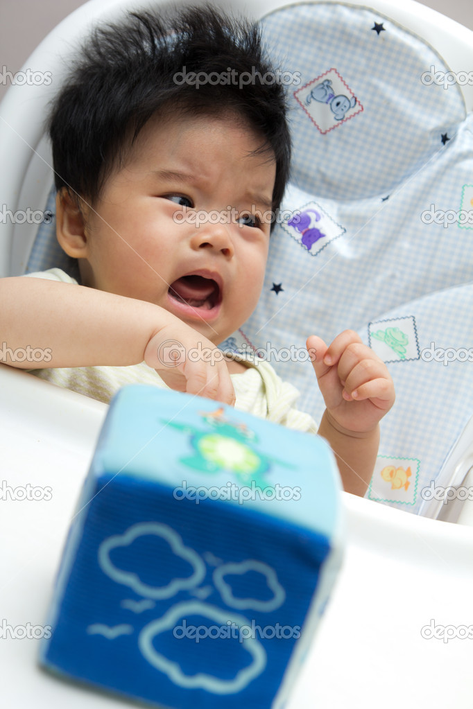 Little Asian baby girl crying on a high chair  Stock Photo #6682680