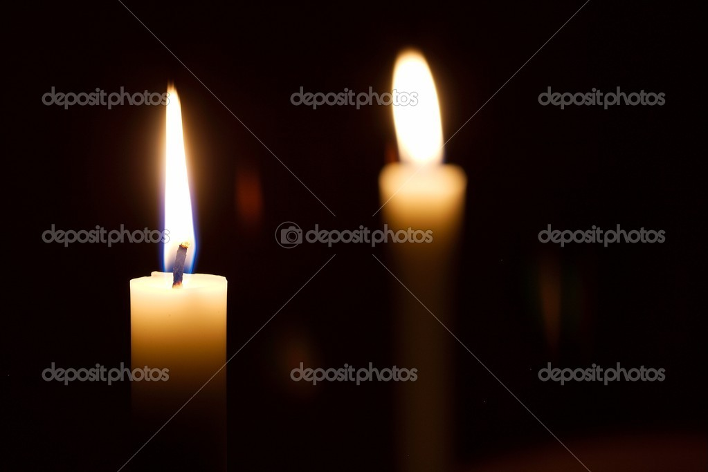 Burning candles in the dark, one of them in focus — Stock Photo #5491853