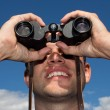 Stock Photo: Young man looking with binoculars, blue sky