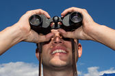 Young man looking with binoculars, blue sky — Stock Photo