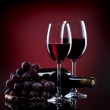 Wine in glasses with grape and bottle on red — Stock Photo