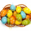 Color easter eggs in basket isolated on white. top view — Stock Photo