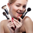 Young smiling woman with make up brushes isolated on white - Stock Photo