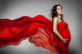 Pregnant woman in red dress — Стоковое фото