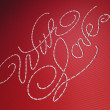 Stock Photo: With love embroidery words on red