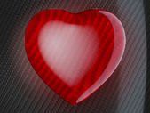 Red heart shape on carbon fiber — Stock Photo