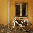 Old bicycle against wall — Stock Photo