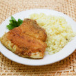 Fried breaded tilapia served with rice and herbs — Stock Photo