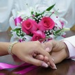 Stock Photo: Hands of newlyweds and bridal bouquet