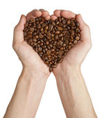 Heart shape made from coffee beans in hands — Stock Photo