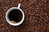Taza de café sobre fondo de frijoles — Foto de Stock