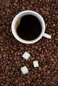 Tazza di caffè con zucchero su fagioli arrostiti — Foto Stock