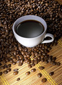Coffee cup with roasted beans — Stock Photo