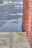Puddles in Parking Lot with Brick Building — Stock Photo
