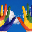 Painted  hands on blue sky background. — Stock Photo