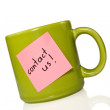 "Cup with note ""contact us!"". — Stock Photo"