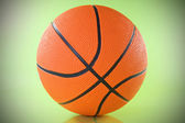 Basketball ball over a green background. — Stock Photo