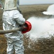 Fire in a silver protective suit. — Stock Photo