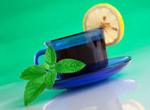 Nice cup of tea and mint on green background — Stock Photo