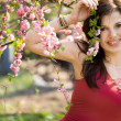 Woman in garden with pink flowers - Stockfoto