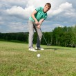 Golf green hole course man putting ball inside short putt - Stock Photo