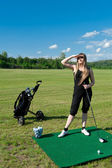 Woman about to strike golf ball — Stock Photo